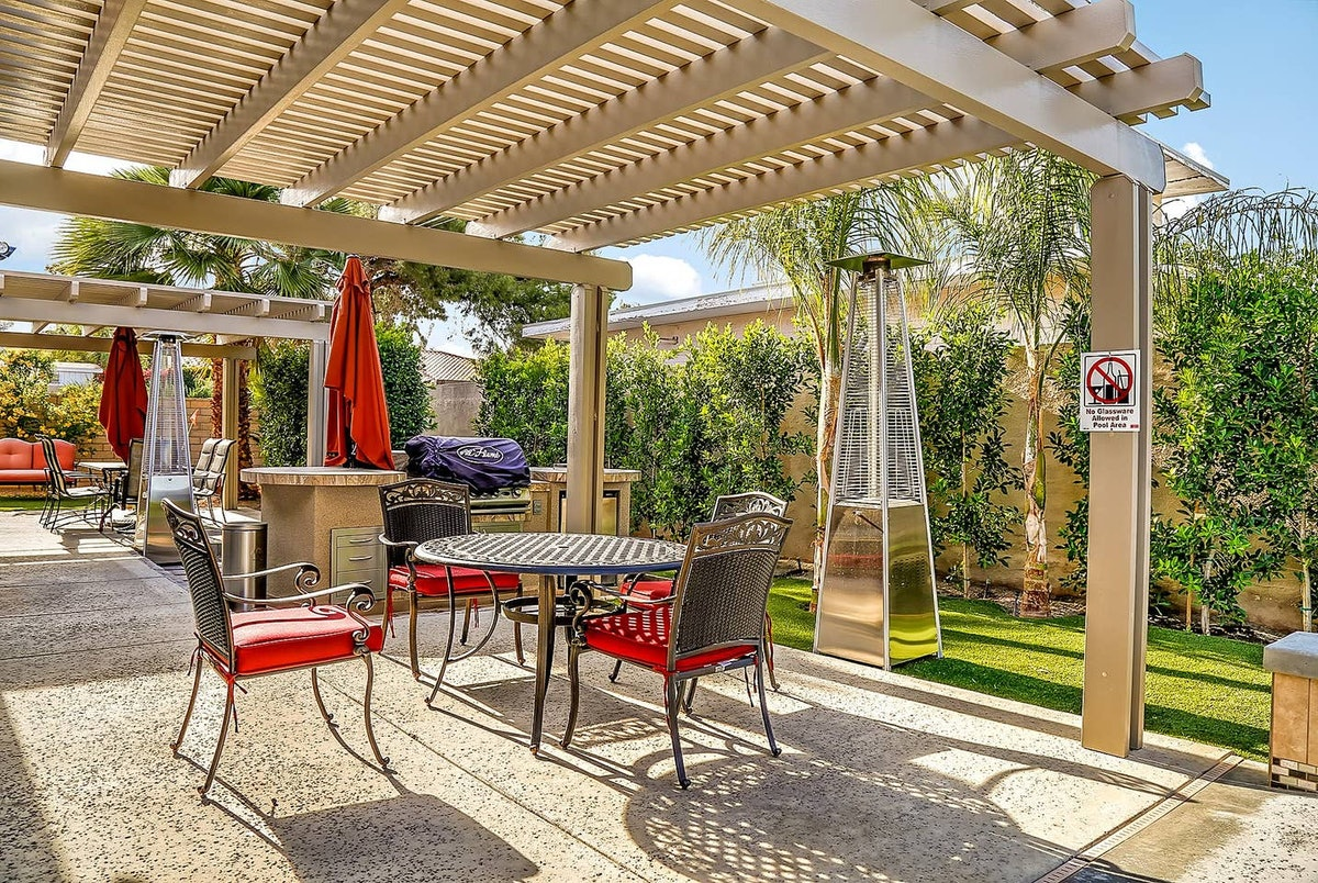A outdoor table and chairs with a grill sit in the backyard of a Palm Springs Airbnb.