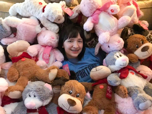 A picture of a smiling girl amidst a sea of plush toys.