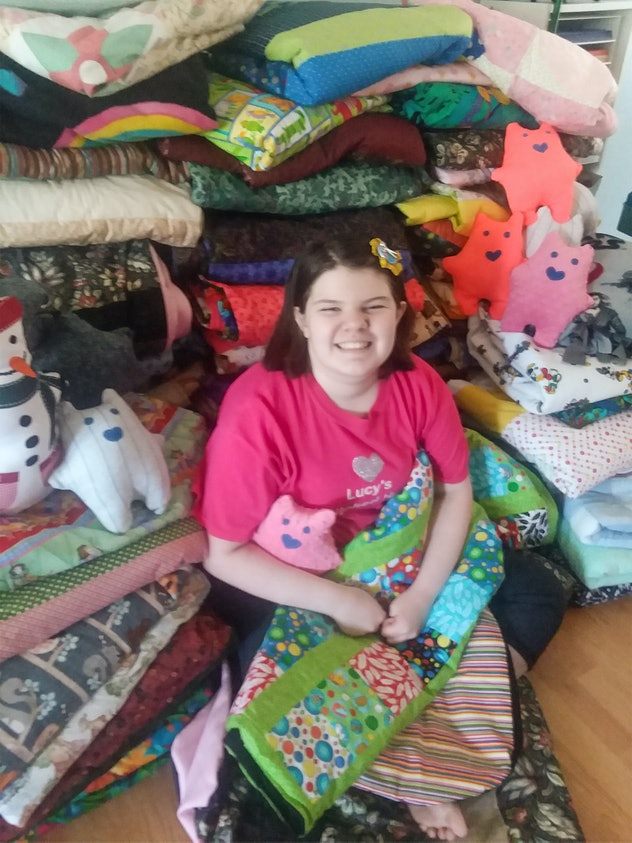 A picture of a smiling girl surrounded by quilts.