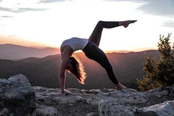 Young woman stretching at sunrise