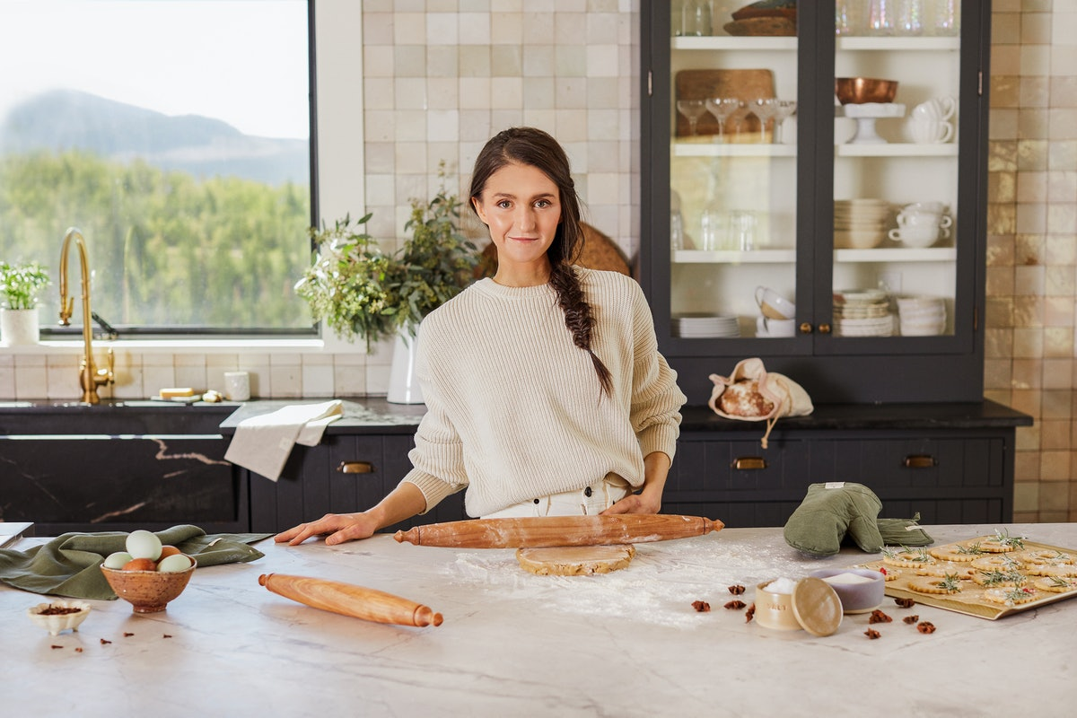 A woman stands in the kitchen with the Etsy x Half Baked Harvest Collection, baking for the holidays.