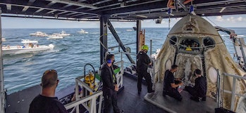 Onlookers watch SpaceX's recovery team open the hatch to the Crew Dragon spaceship.