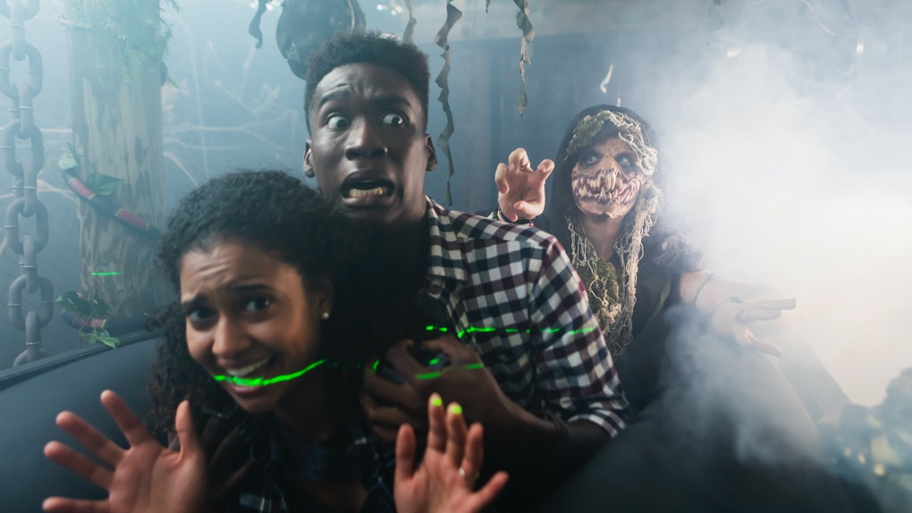 Young man & woman in haunted house on Halloween with zombie