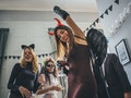 Young woman partying in devil's costume on Halloween before posting on Instagram with a clever capti...