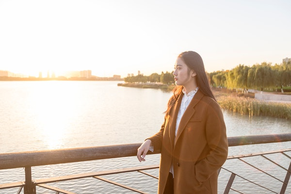 Young woman standing on a bridge in fall