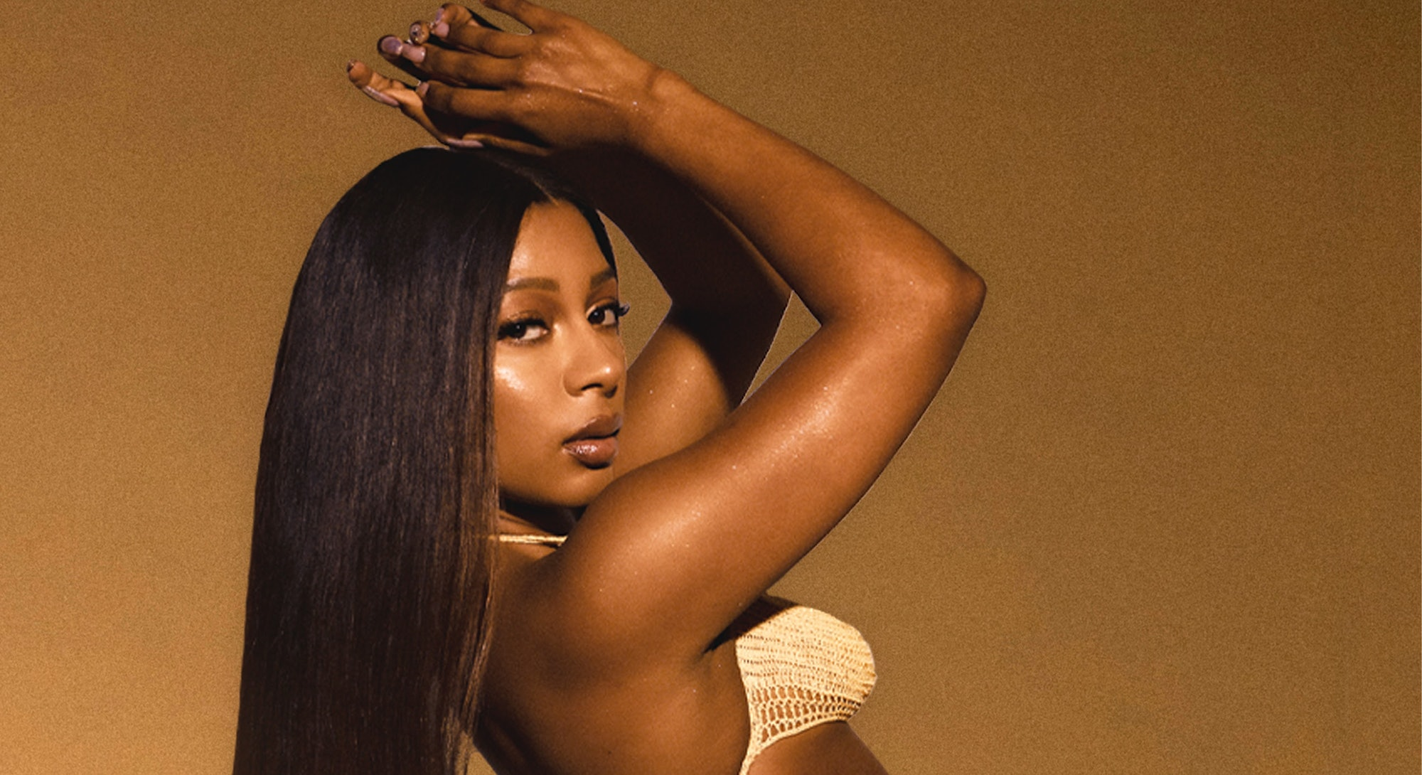 Victoria Monét poses with her hands clasped above her head.