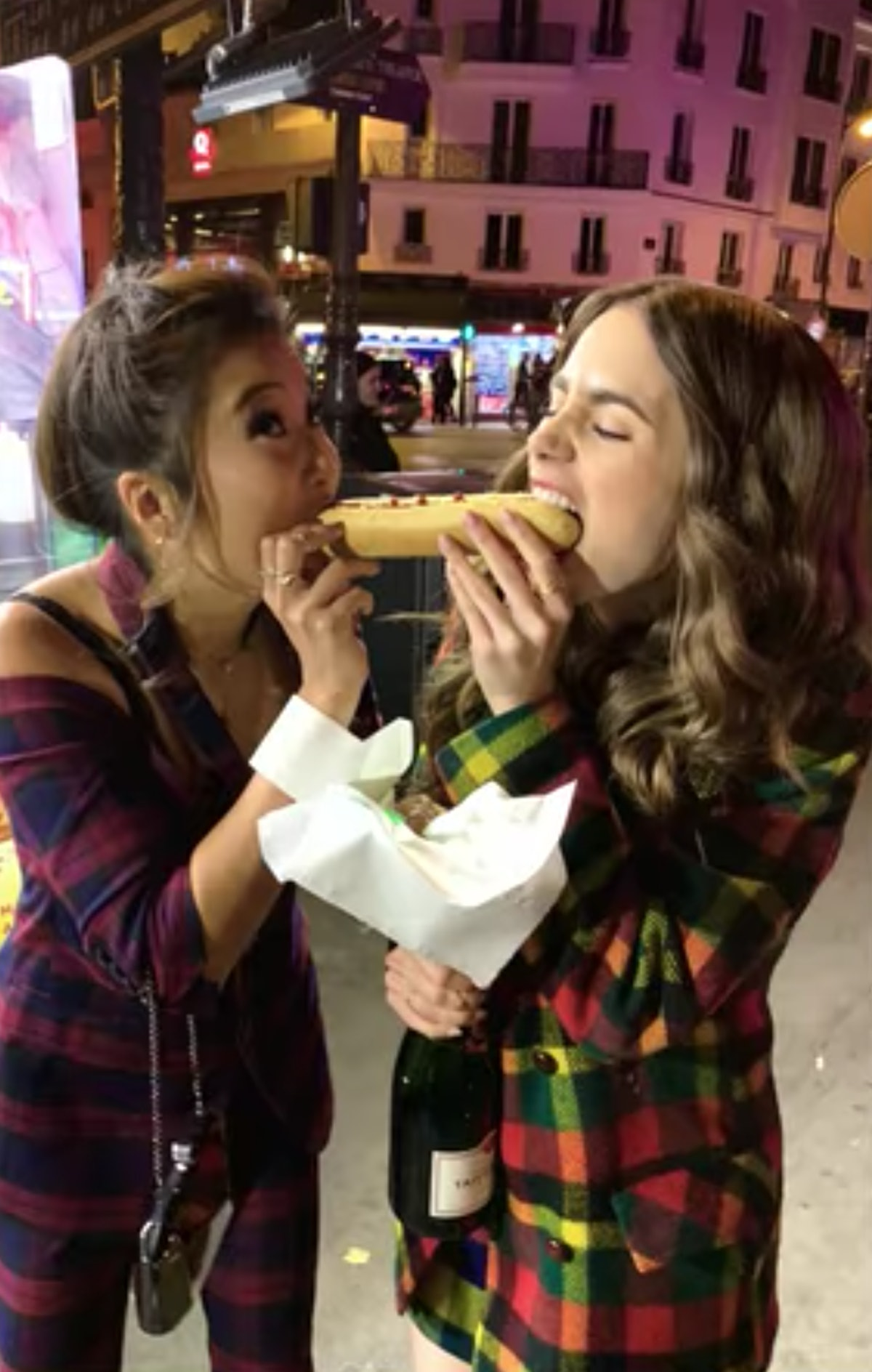 Emily (Lily Collins) and Mindy (Ashley Park) bite out of a hot dog at the same time like in 'Lady an...
