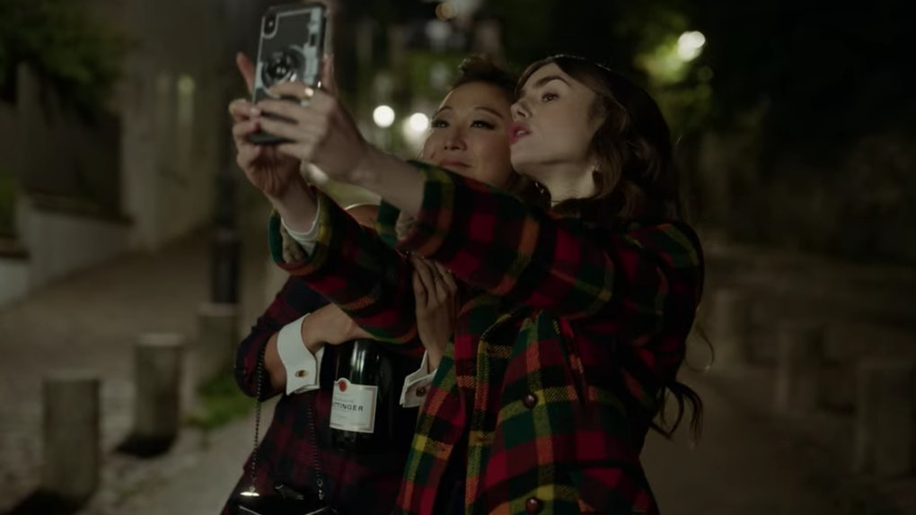 Emily (Lily Collins) and Mindy (Ashley Park) pose for a selfie in Paris at night.