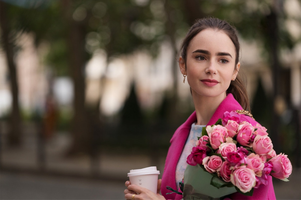 Emily from 'Emily in Paris' wears a hot pink pea coat and holds a coffee cup and bouquet of roses.