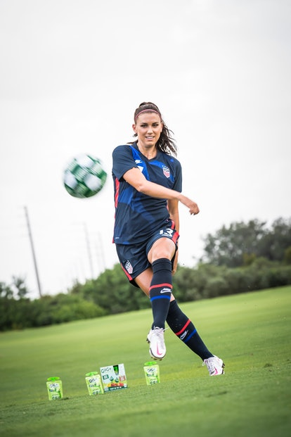 Professional soccer player Alex Morgan kicks a ball around on the field near a box of GoGo SqueeZ snack packs.