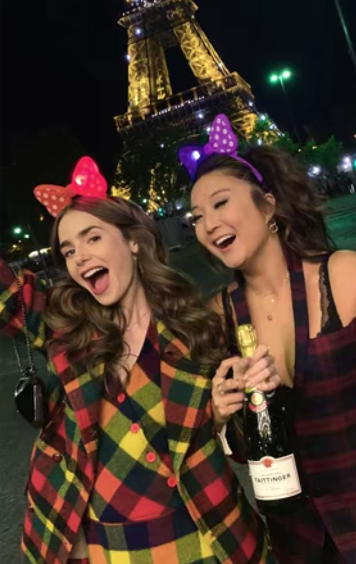 Emily (Lily Collins) and Mindy (Ashley Park) pose with a bottle of champagne in front of the Eiffel ...