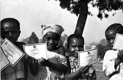 Children in Cameroon show off their smallpox vaccination certificates in 1975.