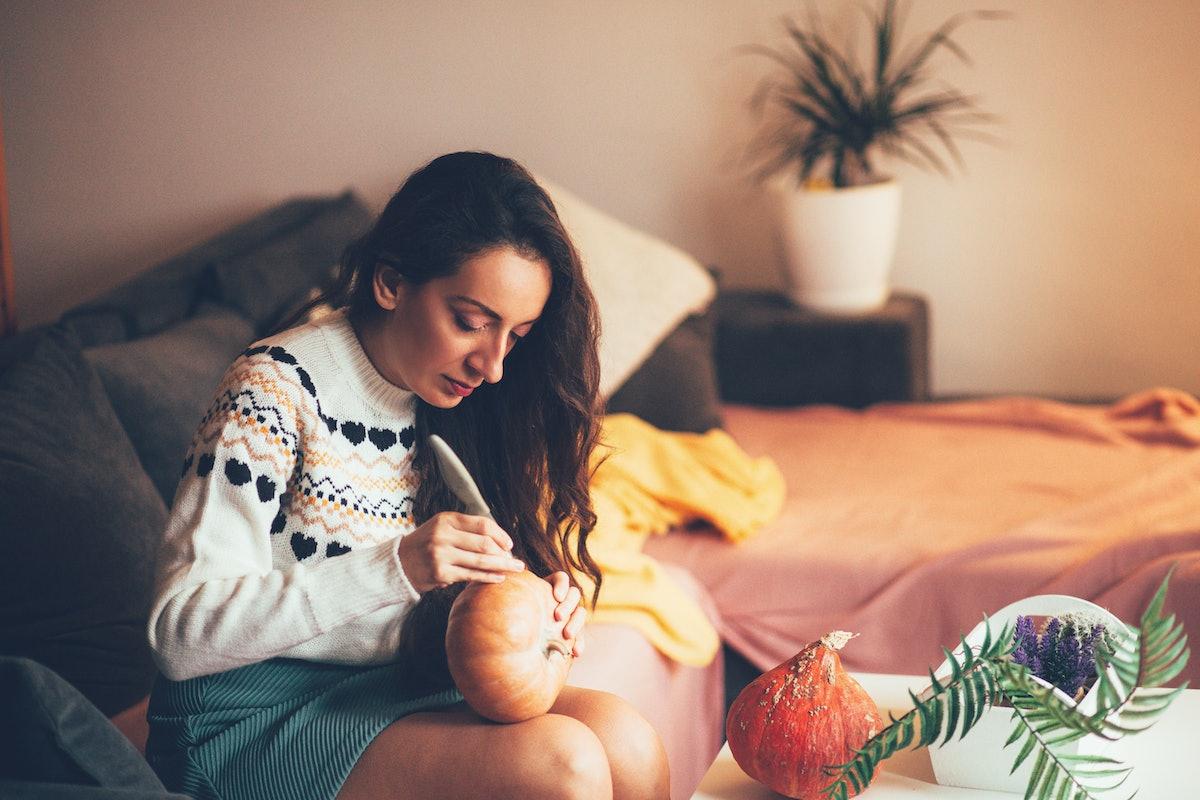 Young woman carving pumpkin