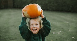 little girl holding a pumpkin on her head. Experts say pumpkin picking is best the first two weeks of October.