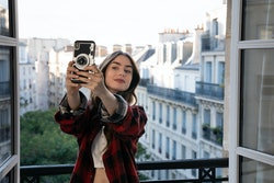 LILY COLLINS as EMILY in episode 101 of EMILY IN PARIS, shown taking a selfie on her balcony in Par...