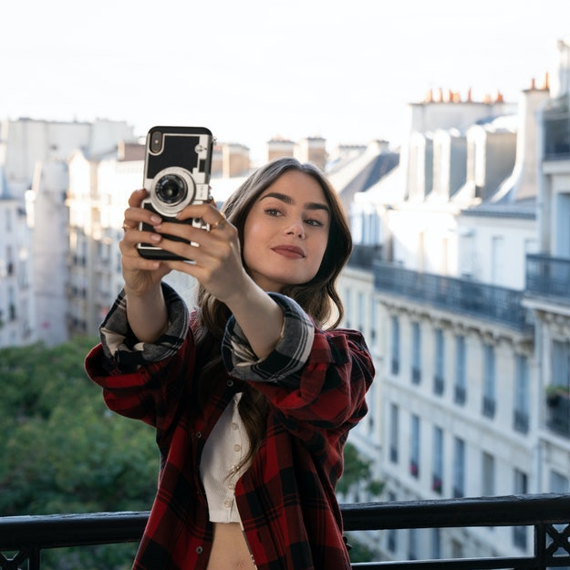 LILY COLLINS as EMILY in episode 101 of EMILY IN PARIS, shown taking a selfie on her balcony in Paris.