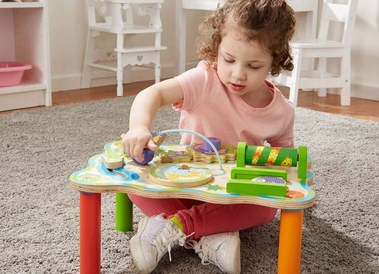little girl sitting at a melissa & doug table