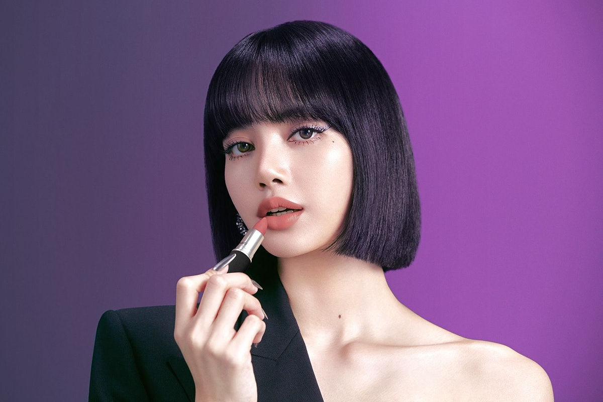 Lisa from BLACKPINK in MAC campaign photo applying lipstick.