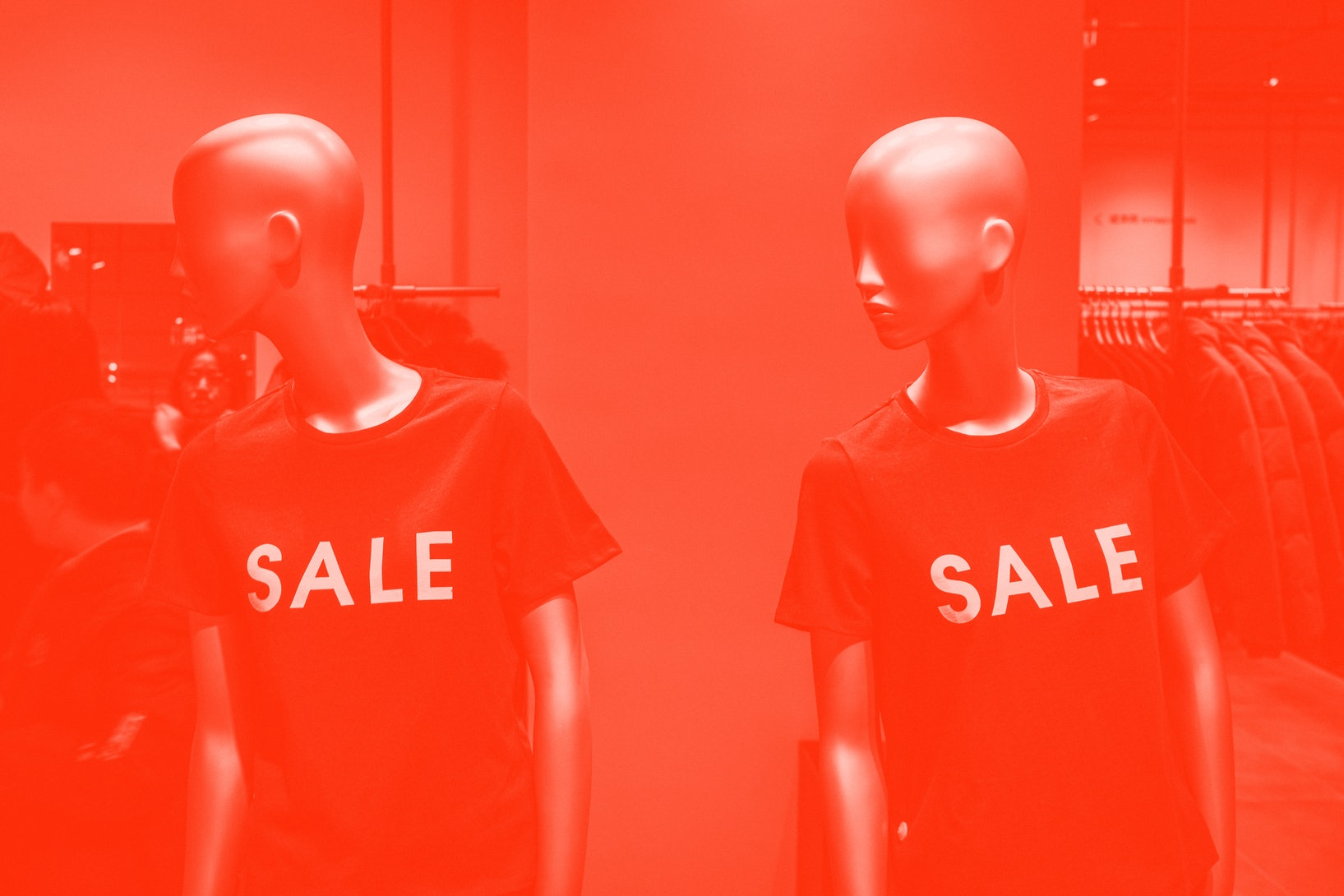 """Two mannequins are positioned side by side, wearing T-shirts that read """"SALE."""""""