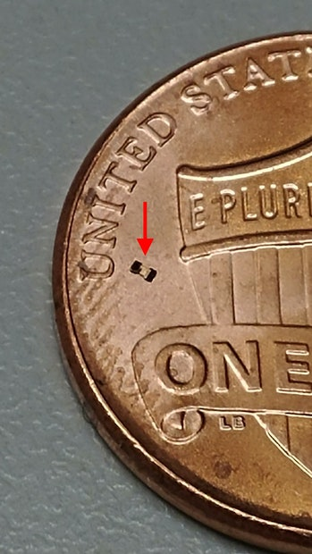 "A microrobot next to the ""U"" of the United States on a penny's tails side"
