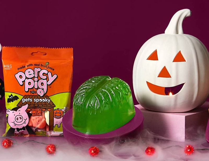 A bag of percy pig gets spooky sweets, a jewlly zombie brain, and a white pumpkin lantern arranged against a purple backdrop with smoke