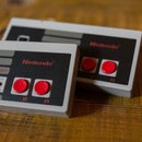 Two NES (Nintendo Entertainment System) Classic Mini controllers.