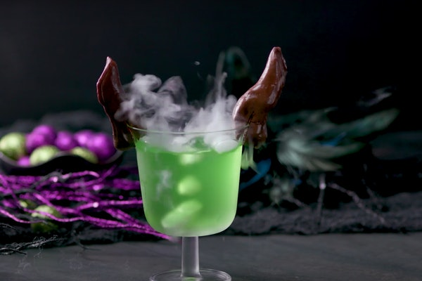 A Maleficent green drink with chocolate horns sits on a table decorated for Halloween.