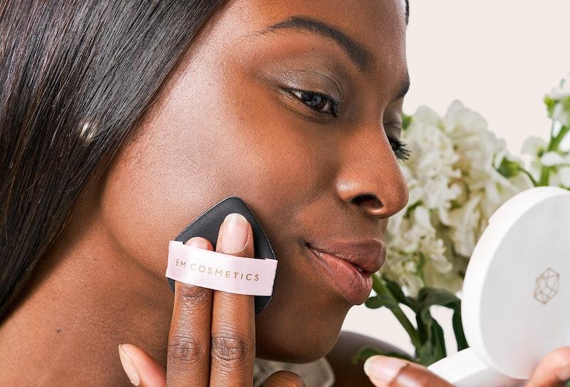 Model applying EM Cosmetics' new Daydream Cushion with puff applicator.