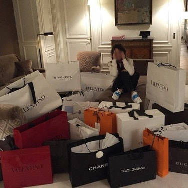 A photo of an influencer surrounded by shopping bags.