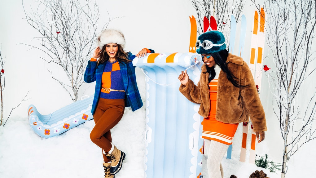 Two young women pose next to new pieces from the FUNBOY winter 20/21 SNOW collection while wearing colorful jackets and clothes.