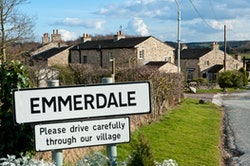 An emmerdale road sign outside a picturesque village