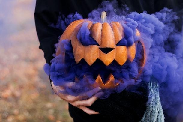 A face carved in an orange pumpkin. halloween deco. Halloween orange pumpkin smoking with purple smoke. live pumpkin head. monster party