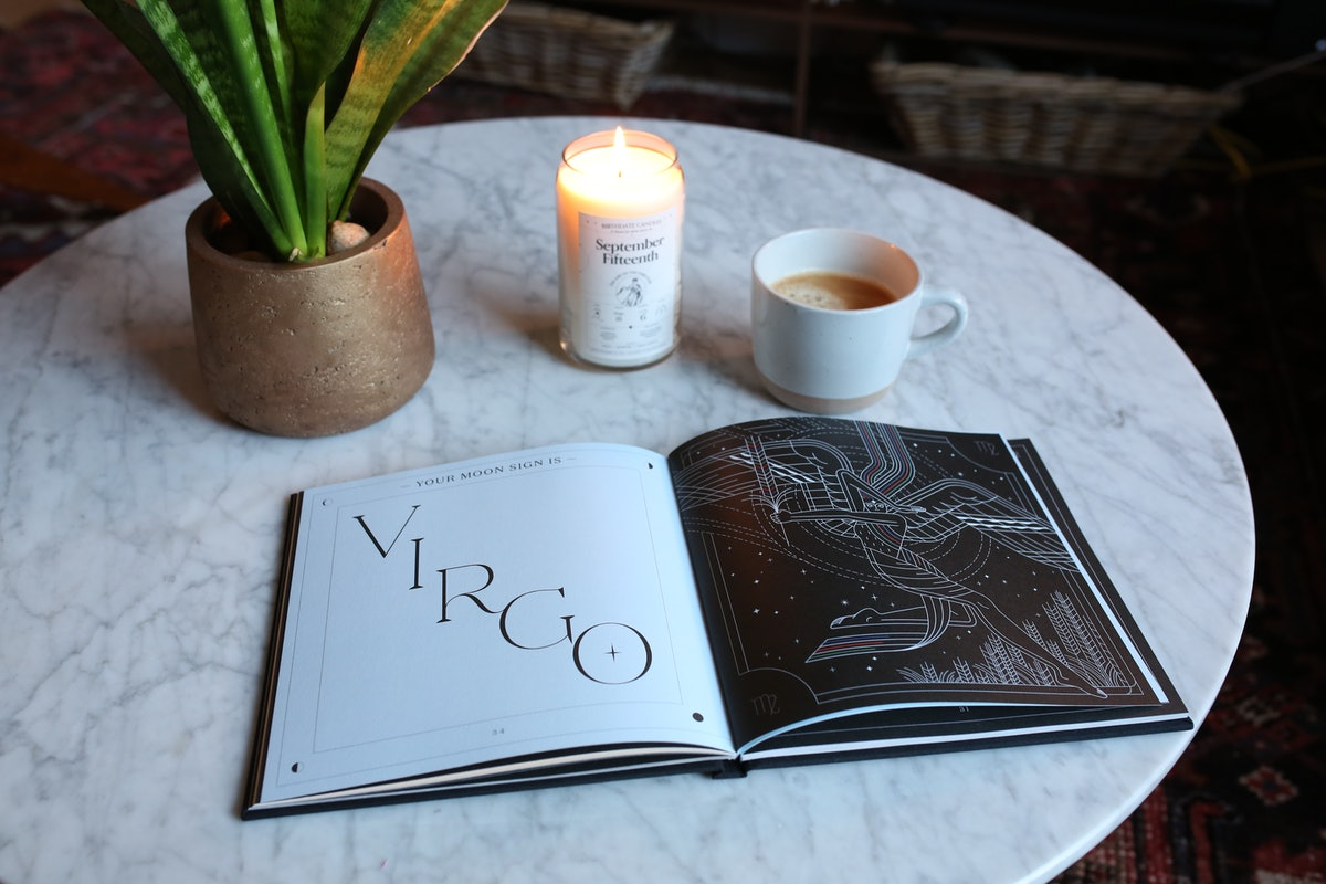Birthdate Co.'s 'Birthdate Book' is opened up on a marble coffee table next to a celestial candle and succulent.