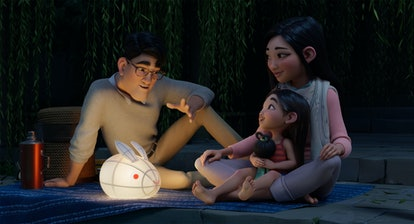 In a still from the film, a young girl sits n her mother's lap, as they look at her father.