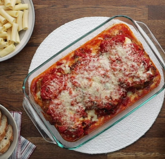 Dr. Jill Biden's chicken parm in baking dish, on a table with bread and pasta noodles to the side