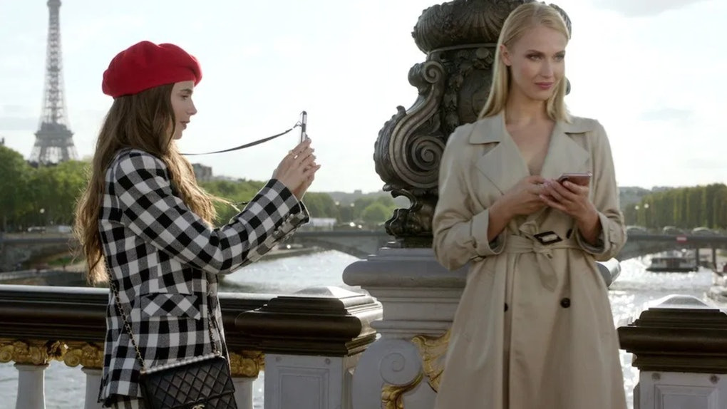 Emily (Lily Collins) snaps a picture of a model on the Pont Alexandre III bridge in Paris.