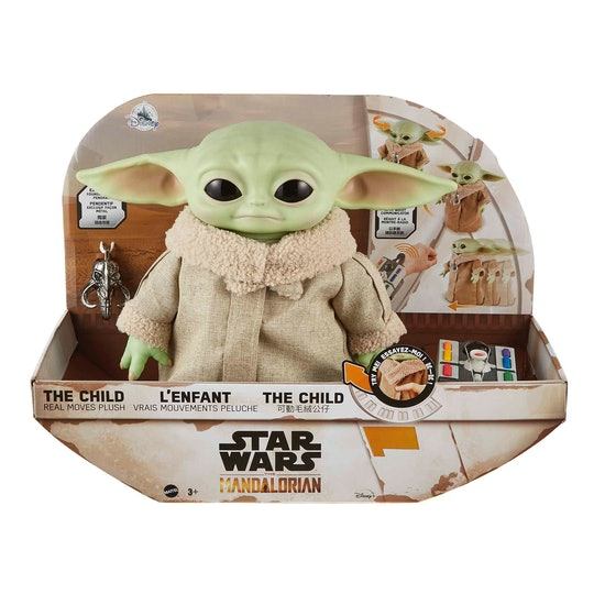 An image of a Baby Yoda plush in a box with a pendant and remote control.