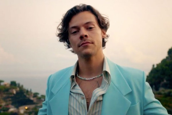 Harry Styles dressed in a teal suit, stands in front of the ocean on the Amalfi Coast.