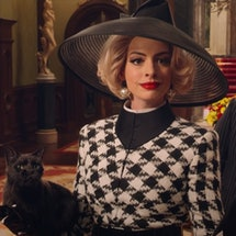 Anne Hathaway dressed in a black and white houndstooth suit with a black hat and pearl earrings. Very chic.