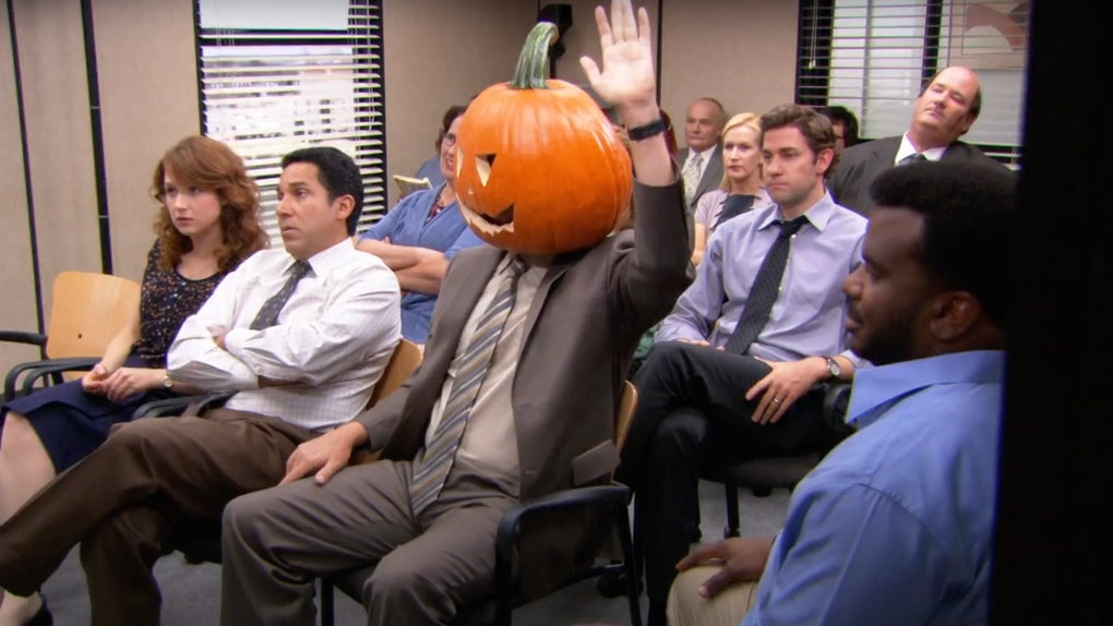 Dwight Schrute sits in the conference room during a Halloween episode of 'The Office' with a pumpkin on his head.