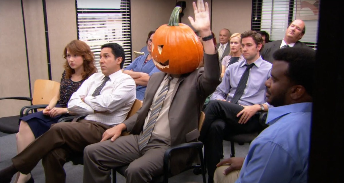 Dwight Schrute sits in the conference room during a Halloween episode of 'The Office' with a pumpkin...