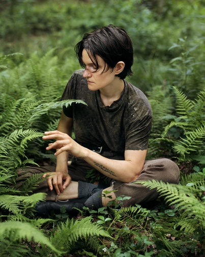 Singer-songwriter Adrianne Lenker sits among fern on the forest floor, gently touching the tip of a leaves.
