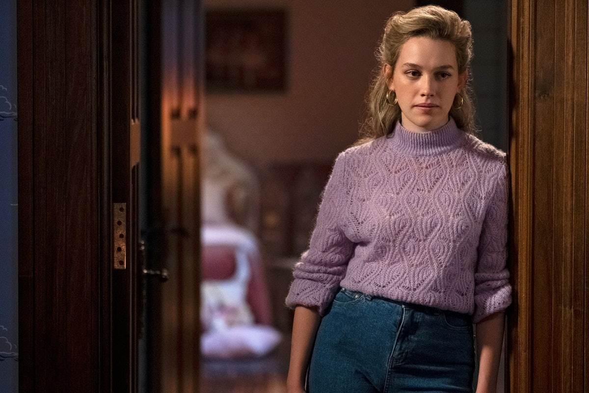 """Dani, from """"Bly Manor,"""" standing in a doorway in mom jeans and a purple sweater."""
