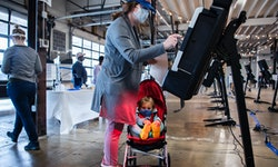A voter and her daughter fill out a ballot in a Super Vote Center at Union Market during early voting in Washington, D.C., on Tuesday, October 27, 2020.