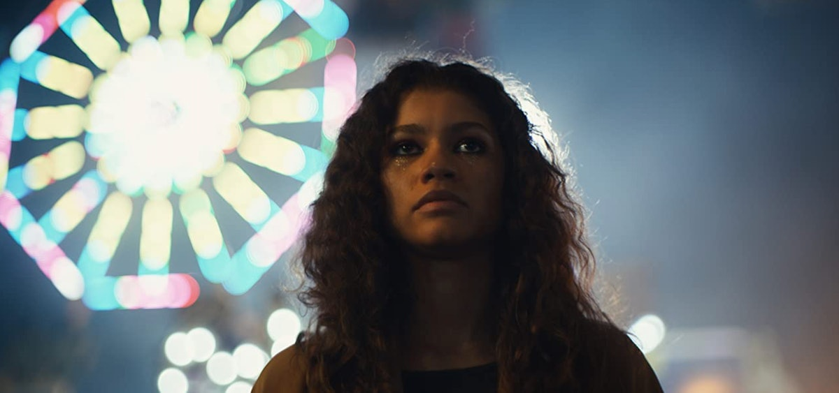 Zendaya stands next to an illuminated Ferris wheel while wearing glitter makeup in a scene of HBO's ...