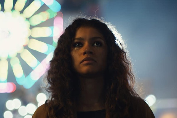 Zendaya stands next to an illuminated Ferris wheel while wearing glitter makeup in a scene of HBO's 'Euphoria.'