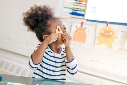 A little Black child with a cute ponytail in school, holding up an wooden letter A and peeking through it.