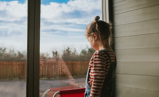 A child crying and looking outside — experts say you can validate their emotions to make them feel better.