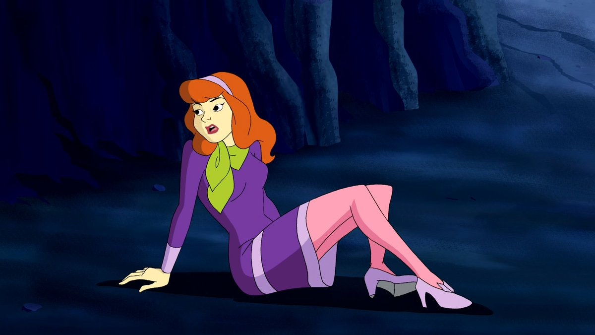 """Daphne Blake from """"Scooby Doo"""" lays on the ground of a cave in distress."""