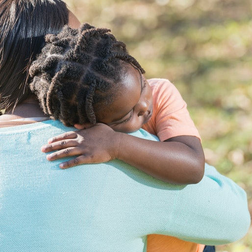 Close up of an African American mother hugging her 4 year old son. His eyes are closed and he has a serious expression on his face. He is sad, or perhaps taking a nap and resting his head on his mother's shoulder.